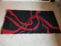 As new solid wooden shaggy rug red and black modern and stylish great condition