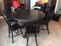 Black circular dining table and 6 chairs