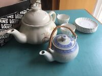 Two teapots with small cups
