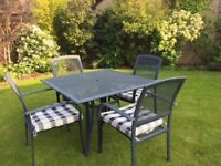 Black metal garden table, 4 chairs and chshions - can stay outside all year.