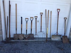 Several outdoor shovels, hoes, rakes and brooms