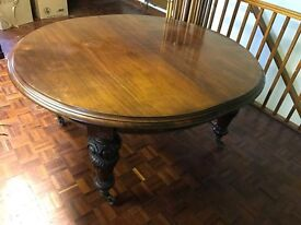 11 foot long Oak Dining Table with extending leafs, carved legs and brass wheels