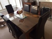 Wooden Dining room table, rectangular, with 6 brown leather dining chairs. Toughened glass cover