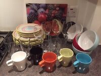 assortment of colourful bowls, dinner & side plates, glasses, mugs, wine glasses , chopping board