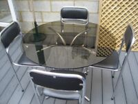 REDUCED FOR CHRISTMAS. VINTAGE RETRO SMOKED GLASS ROUND TABLE & 4 ORIGINAL CHAIRS SOUDEX VYNYL
