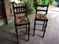 Two solid wood bar stools with rattan seats