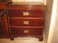 Solid wood chest of drawers with inlaid brass handles.
