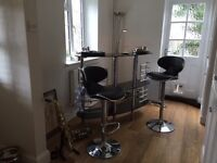 Black glass and chrome bar and two height adjustable bar stools