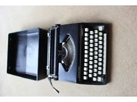 Portable manual typewriter in carry case. Made by Silver Reed model Silverette