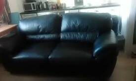 Two large black leather sofas