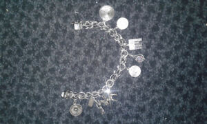 REAL SILVER MARKED 925 CHARM BRACELET WITH MANY CHARMS.