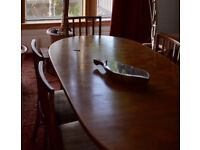 Extending dining table with six upholstered chairs