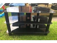 Black glass TV stand in overall good used condition.