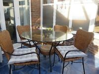 Round glass topped table and four chairs with cushions. Table sits on metal frame with small shelf.