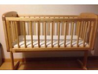 Swinging crib with unused bedding