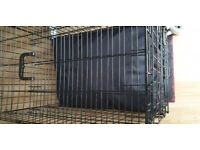 Dog crate with dog bed inside