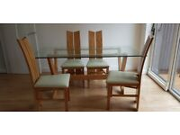 Glass dinner table with four leather chairs