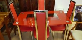 Lovely red glass dining table and 4 chairs . Excellent condition