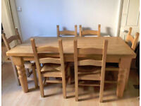 Farmhouse style solid beech dining table in good condition with 6 strong Breton rattan seat chairs