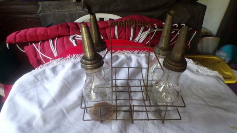 4 ANTIQUE GLASS MOTOR OIL BOTTLES WITH ANTIQUE WIRE RACK