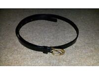 Women/ladies black leather/pvc skinny/thin/slim belt with a gold buckle fastening