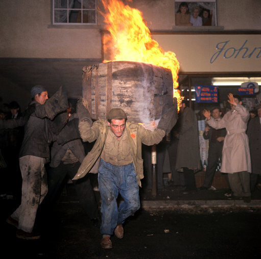 A man carries a burning barrel through the streets of Ottery St Mary in 1963. PA