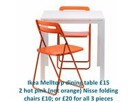 Ikea Melltorp white dining table and 2 pink Ikea Nisse folding chairs