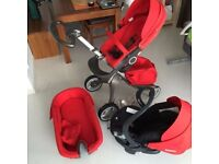 Red stokke xplory travel system includes car seat and isofix base