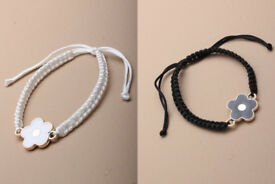 Corded bracelet with enamel daisy charm. In black or white. - JTY133