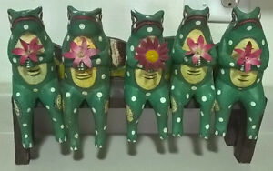 Green Wooden Frogs Sitting on a Wooden Bench with Flowers