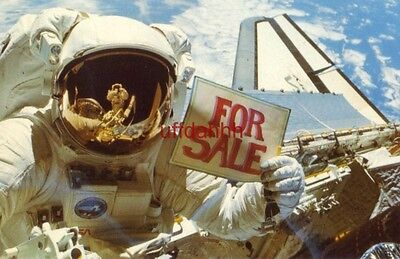 """ASTRONAUT DALE A. GARDNER HOLDS UP A """"FOR SALE"""" SIGN after completing an EVA"""