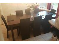 Dark Walnut extending dining table and 8 black faux leather chairs