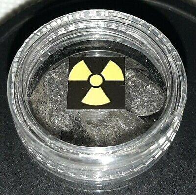 Clear plastic container of uranium ore. Pitchblende. Active. Geiger counter.