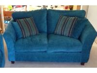 Teal turquoise two seater sofa.