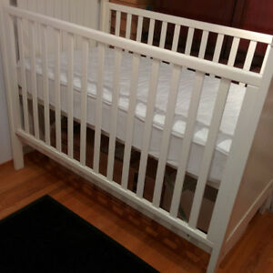Baby crib, adjustable heights, with dual-purpose mattress.