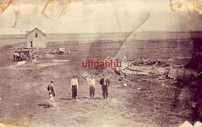 FOUR MEN AND A CHILD STAND IN FRONT OF DESTRUCTION note reads No. Dakota tornado