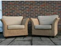 Two beige banana leaf arm chairs
