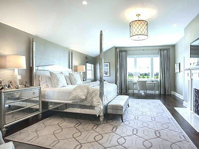 Layers of fabric used on the curtains and bedlinen softens the look of this bedroom