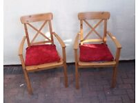 Two Ikea Pine Dining Room Chairs with arms and seat pads