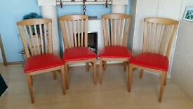 4 great dining room chairs with a red seat.