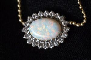Opal , surrounded by diamonds, gold chain.