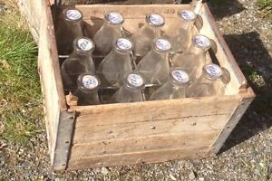 Vintage glass milk bottles with wooden crate
