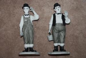 Laurel and Hardy porcelain figurines on wooden bases.