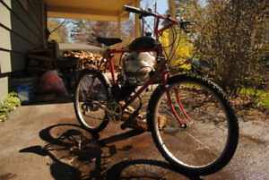 Motorized bicycle. Small engine on old school red mountain bike.