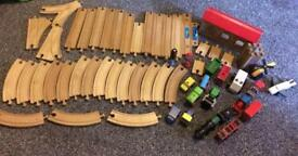 Wooden train track with lots or cars and trains