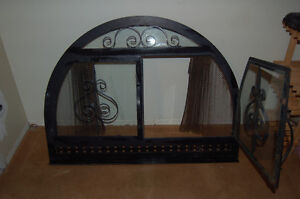 Rounded fireplace cover with glass doors and screen.