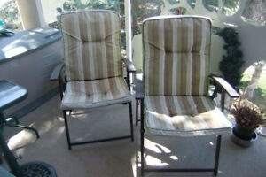 two metal folding patio chairs