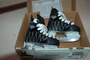 Two pairs of kids CCM skates and Bauer helmet with cage
