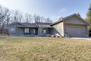 Custom built ranch on spacious lot backing onto  forest