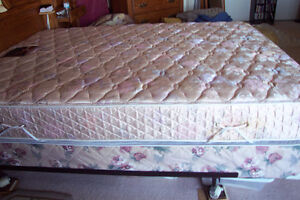 Queen size mattress and box spring and frame on wheels in